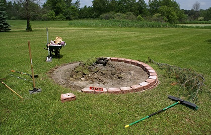 The fire pit being constructed around the old burn pile.