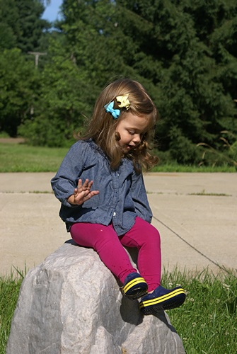 Madeline Eloise sitting on our fake rock in our front yard (it's the cover for our well).