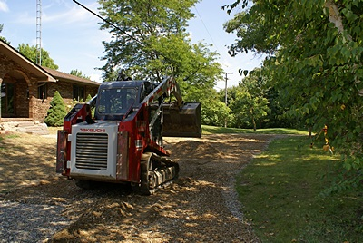 Spreading 21AA road gravel to fix the driveway.