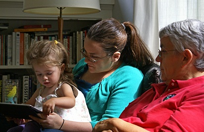 Madeline being read to by Aunt Meghan with Grandma Linda.