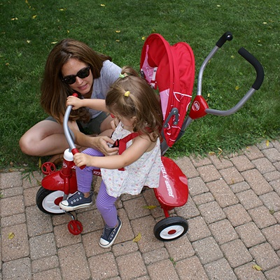 Madeline shows her new tricycle to he mommy.  It's not a Subaru, but it's pretty cool.