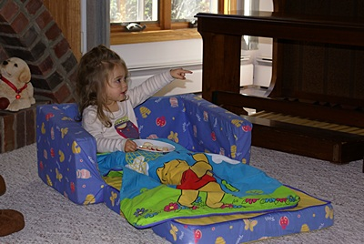 Madeline in her sofa-bed with her Winnie-the-Poor sleep sack.