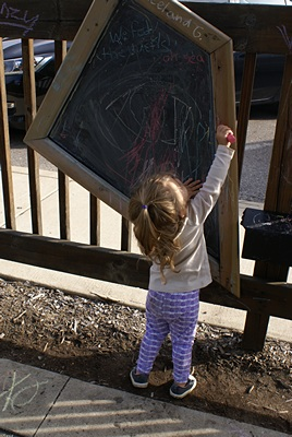 Madline working with chalk at the Brighton Mill Pond playscape.