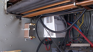 Stacked plate heat exchanger to left of Magnum 4024 inverter/charger.