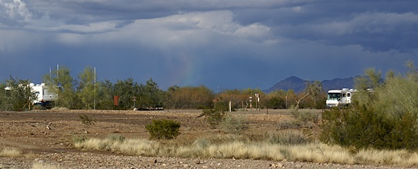 Rainbow colors refract from the rain near the center of this scene.  AZ-95 looking NE over the Plomosa Rd BLM STVA.