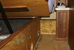 The area just forward of the bed base with the bed platform raised and facing the driver side of the bus.