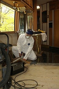 Me in the Tyvek jumpsuit removing the black ceramic floor tiles.  (Photo by Linda.)