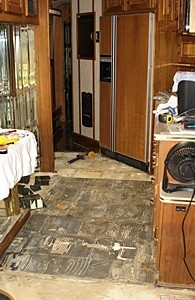 View of kitchen floor looking toward rear from living room.  Black Ceramic tile has been removed to just past the refrigerator.