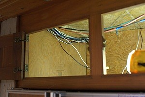 The cabinet above the refrigerator in our bus with the inside panels removed revealing lots of wiring.