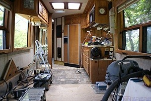 The interior of the bus deconstructed in preparation for a new floor, seating, and custom desk.