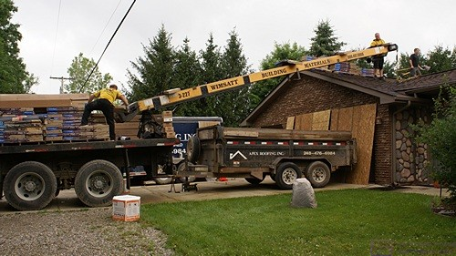 Wimsatt unloads shingles onto the garage roof.