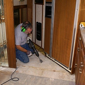 Me using the Makita 11 lb power chisel to remove thinset and mastic from the floor of our H3-40.  (Photo by Linda)