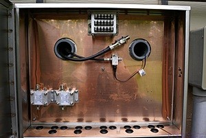 Cable entry box showing copper ground plane with Morgan lightning arrestors (lower left), control line arrestor (center top), and cellular and OTA TV arrestors (center).