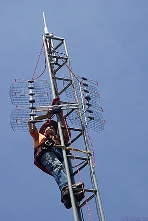 """Installing the DB8e OTA TV antenna required three hands.  Note that I am installing it at the highest point possible when suspended from the pulley with the haul rope in an inverted """"Y"""" attachment.  (Photo by Linda)"""