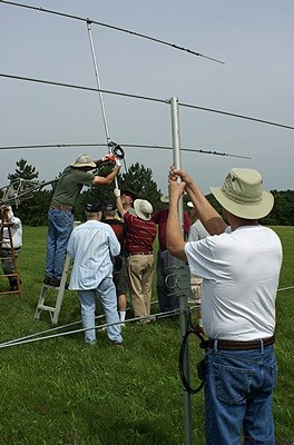 Larry (K8UT) holds the 6m beam while Steve (N8AR) and others attach the 20m beam to the mast of the taller tower.