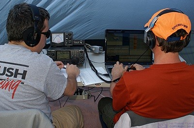Operating stations are often staffed by two people, one operating the radio (left) and the other logging the contacts (right).