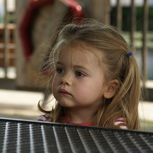 Madeline sitting at a picnic table at the Brighton Mill Pond playscape.