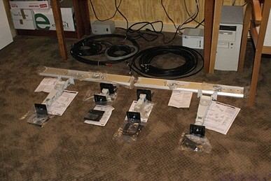 The pieces of the ZioTek monitor mounting system laid out on the floor of the ham shack/office.