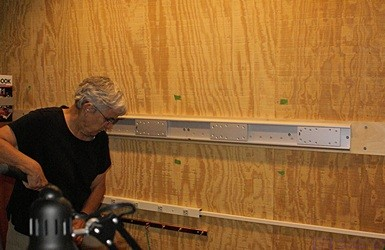 The ZioTek tracks mounted to the poplar board mounted to the wall.  Linda is vacuuming up sawdust from drilling.