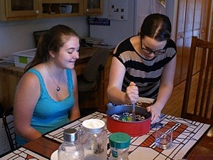 Grand-daughter Katie (L) waiting for a slice of cake baked by her step-mom (our daughter, Meghan, on right).