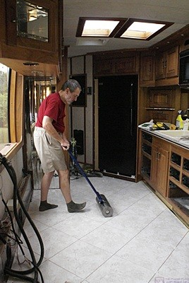 Bruce rolls the floor tiles in the kitchen with the 100 lb. roller.
