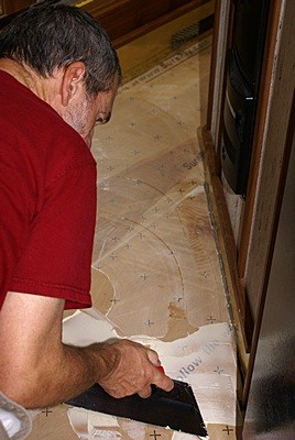 Bruce spreads Armstrong vinyl floor adhesive in the hallway.