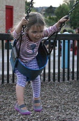 Madeline really enjoys the swings at the Brighton Mill Pond Imagination Station Playscape.