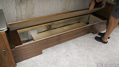 The built-in sofa with the plywood seat raised to reveal the plenum/support boxes on both ends and the center shelf that forms the air return duct for the OTR HVAC.  The empty space will be used for storage.
