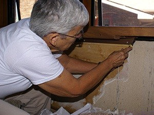 Linda scraps the old wallpaper off below the passenger side living room window.
