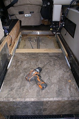 The entrance landing with the floor removed revealing the pneumatic linear actuator that operates the slide out stepwell cover.