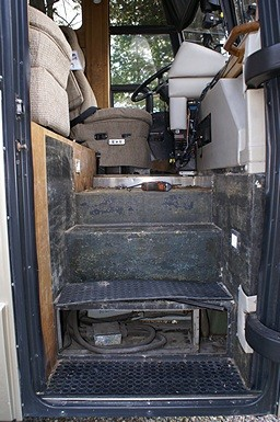 The entry stairs into the bus with the bottom riser cover plate removed to reveal one of the two air-conditioner compressors installed in the spare tire compartment.  This is how the ports are accessed for service and recharging. The other compressor is accessed through the bay under the driver's seat.