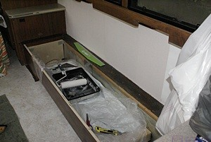 Wallpaper tools in sofa (seat removed) and wallpaper on wall behind the sofa.