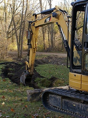 "Another view of Phil's smaller excavator with the 12"" bucket being used to trench the French drain in the southwest portion of our property."