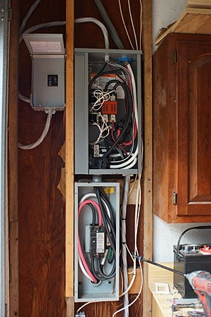 The small box upper left is the new 100 A main disconnect for the electrical panel in the garage.  The large box upper right is the automatic transfer switch and the large box below it is the 200 A service entrance disconnect.