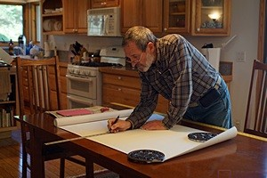 Bruce marks a piece of wallpaper on the dining room table in the house before cutting it.