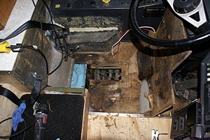 The damaged bus sub-floor cut away.  I could see through into the bay below the driver's seat.  The blue to the left is paper shop towels soaking up the water and rotted plywood in a small tray area.