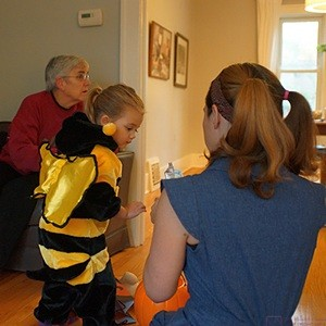 Shawna gets Madeline into her Bumblebee costume for Halloween Trick-or-Treat in their neighborhood.
