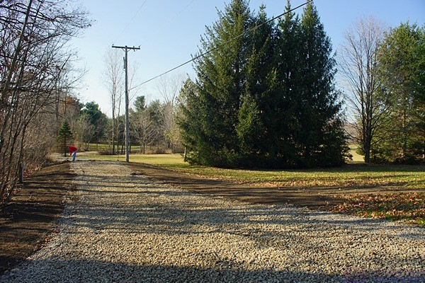 The new gravel driveway extension and RV parking pad.  Phil, on the left side of the driveway by the nearer utility pole, rakes out the topsoil he placed along both sides of the driveway.