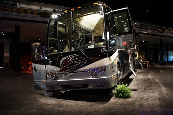 A Prevost H3-45 VIP conversion shell on display at the Tampa RV Supershow.  The driver side of the coach is elevated on ramps and mirrors on the floor allow show attendees to see the underside of the bus.