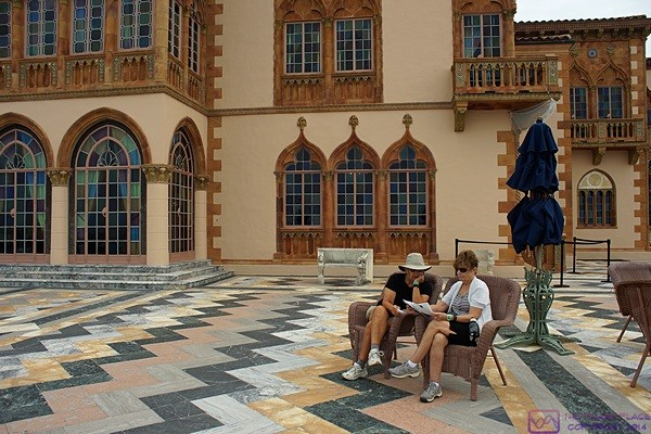 Linda and Karen rest on the patio of Ca' D'Zan and study the map of the Ringling Museums complex, Sarasota, FL.