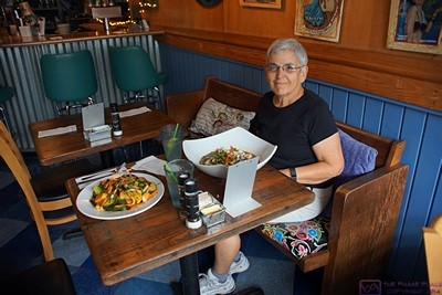 Linda at The Café in Key West, Florida right after our meals had come to the table.  The Café has the Key West look and feel, but was nicer than most of the vegan restaurants we find.  Vegan eateries tend to be near colleges and universities and cater to that clientele, so they do not waste a lot of money on fancy decor.