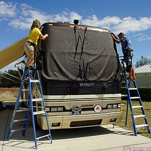 Brenda and Bill test fit the main windshield cover before installing the corner snaps on our Prevost H3-40 motorcoach.  Site #230, Florida Grande Motorcoach Resort, Webster, FL.